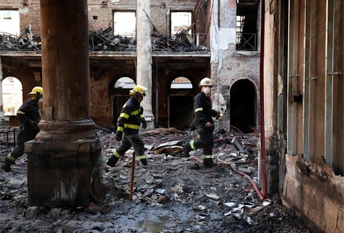 Firemen walk through the burnt out remains of Jagger Library at the University of Cape Town.