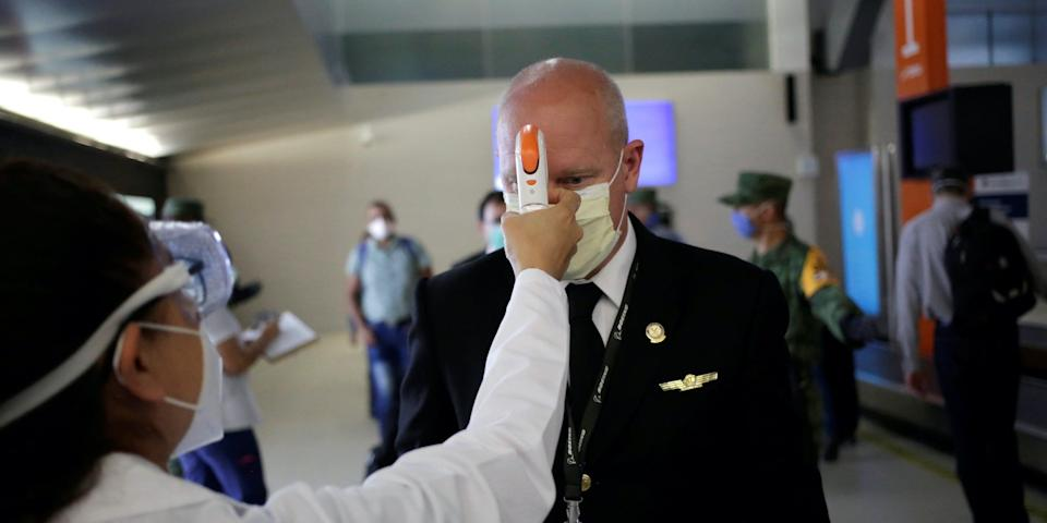 A pilot gets his temperature checked at a sanitary checkpoint on May 18.