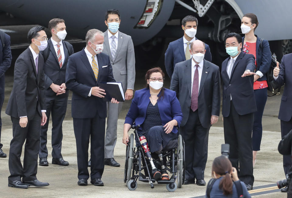 Taiwan's Foreign Minister Joseph Wu, second right, gestures as he welcomes U.S. senators to his right Democratic Sen. Christopher Coons of Delaware, a member of the Foreign Relations Committee, Democratic Sen. Tammy Duckworth of Illinois and Republican Sen. Dan Sullivan of Alaska, members of the Armed Services Committee on their arrival at the Songshan Airport in Taipei, Taiwan on Sunday, June 6, 2021. The three U.S. senators arrived in Taiwan to meet with senior government officials and discuss U.S.-Taiwan relations and other issues in a trip that is likely to anger China, which claims Taiwan as its territory and objects to Taiwan being called a country. (Pool Photo via AP)