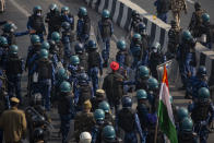 A protesting farmer, wearing orange turban, is let go by riot police as they march to the capital breaking police barricades during India's Republic Day celebrations in New Delhi, India, Tuesday, Jan. 26, 2021. Tens of thousands of farmers drove a convoy of tractors into the Indian capital as the nation celebrated Republic Day on Tuesday in the backdrop of agricultural protests that have grown into a rebellion and rattled the government. (AP Photo/Altaf Qadri)