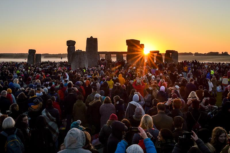 File photo dated 21/06/19 of the sun rising between the stones and over crowds gathered at Stonehenge to celebrate the dawn of the longest day in the UK. English Heritage - which has provided access to the summer solstice celebrations at Stonehenge since 2000 - has cancelled celebrations due to restrictions on mass gatherings to tackle Covid-19, and will instead stream the solstice online.