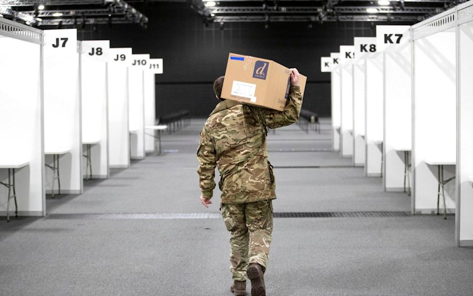 A member of the Royal Scots Dragoon Guard carries in supplies as part of the preparations setting up a mass Covid vaccination centre at the P and J Live Arena in Aberdeen - PA