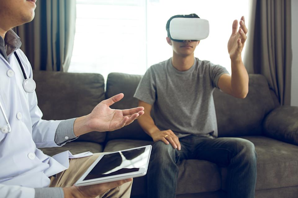 Doctor is using the tablet to send the data to the virtual reality glasses showing the health diagnosis as the patient is wearing and analyzing together at home.