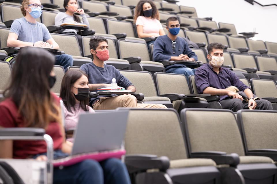 University students in a lecture hall and seated at a socially safe distance.