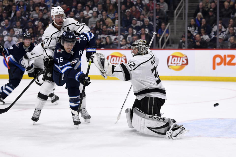 Winnipeg Jets' Mark Scheifele (55) screens Los Angeles Kings goaltender Jonathan Quick (32) as a shot by Nikolaj Ehlers goes in for a goal during the second period of an NHL hockey game Tuesday, Oct. 22, 2019, in Winnipeg, Manitoba. (Fred Greenslade/The Canadian Press via AP)