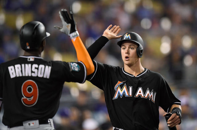 Miami Marlins' Brian Anderson, right, is congratulated by Lewis Brinson after scoring on a double by Cameron Maybin during the ninth inning of a baseball game against the Los Angeles Dodgers on Tuesday, April 24, 2018, in Los Angeles. (AP Photo/Mark J. Terrill)