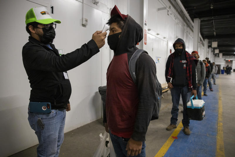 KING CITY, CA - APRIL 28: Migrant farm laborers with Fresh Harvest working with an H-2A visa have their temperature checked and are asked questions about their health before boarding the bus to their shift, in the company living quarters on April 28, 2020 in King City, California. Good accommodations for farm labor is vital but difficult during the coronavirus pandemic. Fresh Harvest houses over 300 laborers in their self-contained King City facility. The laborers are given masks and gloves, and practice social distancing while inside. If anyone experiences health irregularities, they are immediately isolated in different housing and monitored at least twice a day. Medical care from the county is available if further symptoms develop. Accommodations are expensive and difficult to procure for farm labor. Many growers and packers use motels, houses that they purchase and warehouse-style housing. Fresh Harvest is the one of the largest employers of people using the H-2A temporary agricultural worker visa for labor, harvesting and staffing in the United States. The company is implementing strict health and safety initiatives for their workers during the coronavirus pandemic and are trying a number of new techniques to enhance safety in the field as well as in work accommodations. Employees have their temperature taken daily and are also asked a series of questions about how they feel. Despite current record unemployment rates in the U.S. due to COVID-19-related layoffs, there have been few applications to do this kind of work despite extensive mandatory advertising by companies such as Fresh Harvest. (Photo by Brent Stirton/Getty Images)