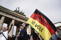 """A participant of a demonstration against the Corona measures holds a German flag with the writing """"We are the people"""", the motto of the 1989 revolution in east Germany, in Berlin, Germany, Saturday, Aug. 29, 2020. (Kay Nietfeld/dpa via AP)"""