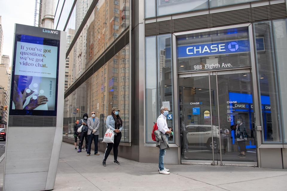 NEW YORK, NEW YORK - MAY 22: People wearing masks wait in line to enter a bank amid the coronavirus pandemic on May 22, 2020 in New York City. COVID-19 has spread to most countries around the world, claiming over 339,000 lives with over 5.3 million cases. (Photo by Alexi Rosenfeld/Getty Images)