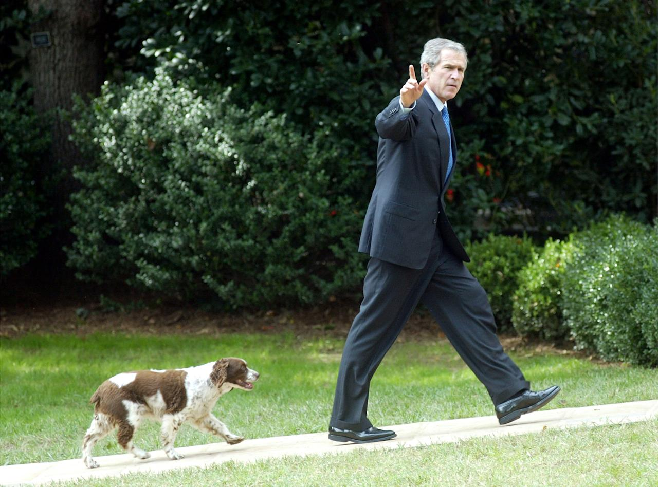 U.S. President George W. Bush waves as he walks toward the Oval Office with his dog Spot September 23, 2002 in Washington, DC. Bush returned from a fund-raiser for Republican Douglas Forrester in Trenton, New Jersey.  (Photo by Alex Wong/Getty Images)
