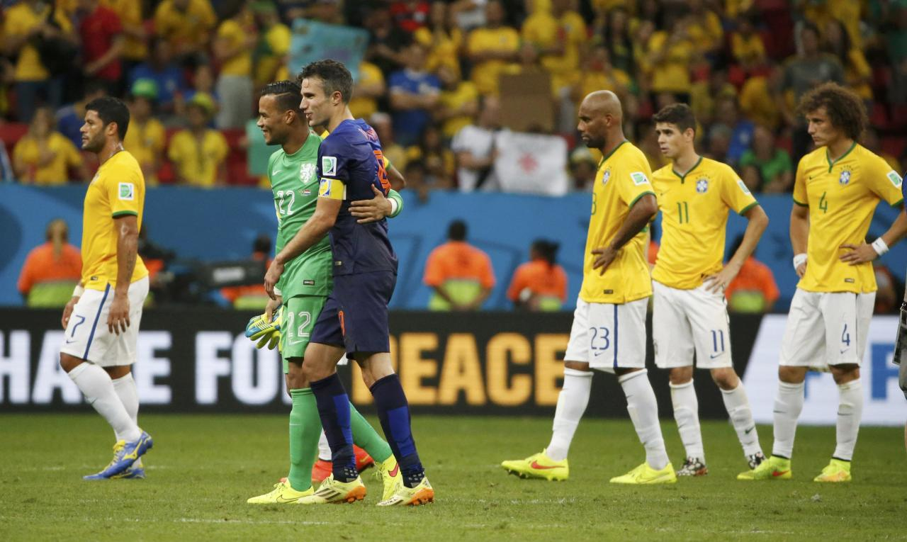 Robin van Persie of the Netherlands walks off the pitch with goalkeeper Michel Vorm, as Brazil players reacts, after their 2014 World Cup third-place playoff at the Brasilia national stadium in Brasilia July 12, 2014. REUTERS/Jorge Silva (BRAZIL - Tags: SOCCER SPORT WORLD CUP)