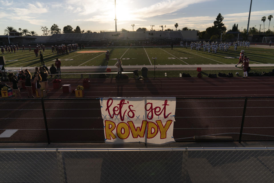A sign hangs on a fence as players warm up before a high school football game between El Modena and El Dorado in Orange, Calif., Friday, March 19, 2021. The team recently played its first football game in a year as more California counties ease coronavirus restrictions and life in the nation's most populous state inches back to normalcy. (AP Photo/Jae C. Hong)