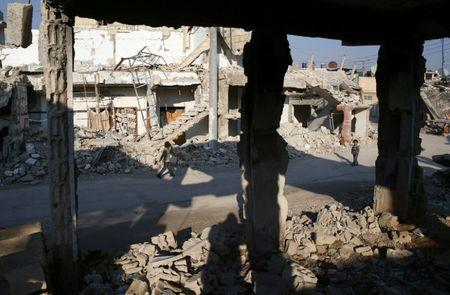 Children walk near damaged buildings in the rebel held besieged city of Douma, in the eastern Damascus suburb of Ghouta, Syria January 7, 2017. Picture taken January 7, 2017. REUTERS/Bassam Khabieh