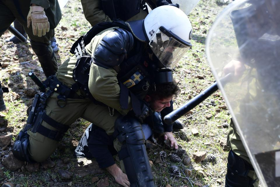 A riot policeman detains a protester during clashes in Karava near the area where the government plans to build a new migrant detention center, on the northeastern Aegean island of Lesbos, Greece, Wednesday, Feb. 26, 2020. Local authorities declared a 24-hour strike on two eastern Greek islands Wednesday to protest government plans to build new migrant detention camps there. (AP Photo/Michael Varaklas)