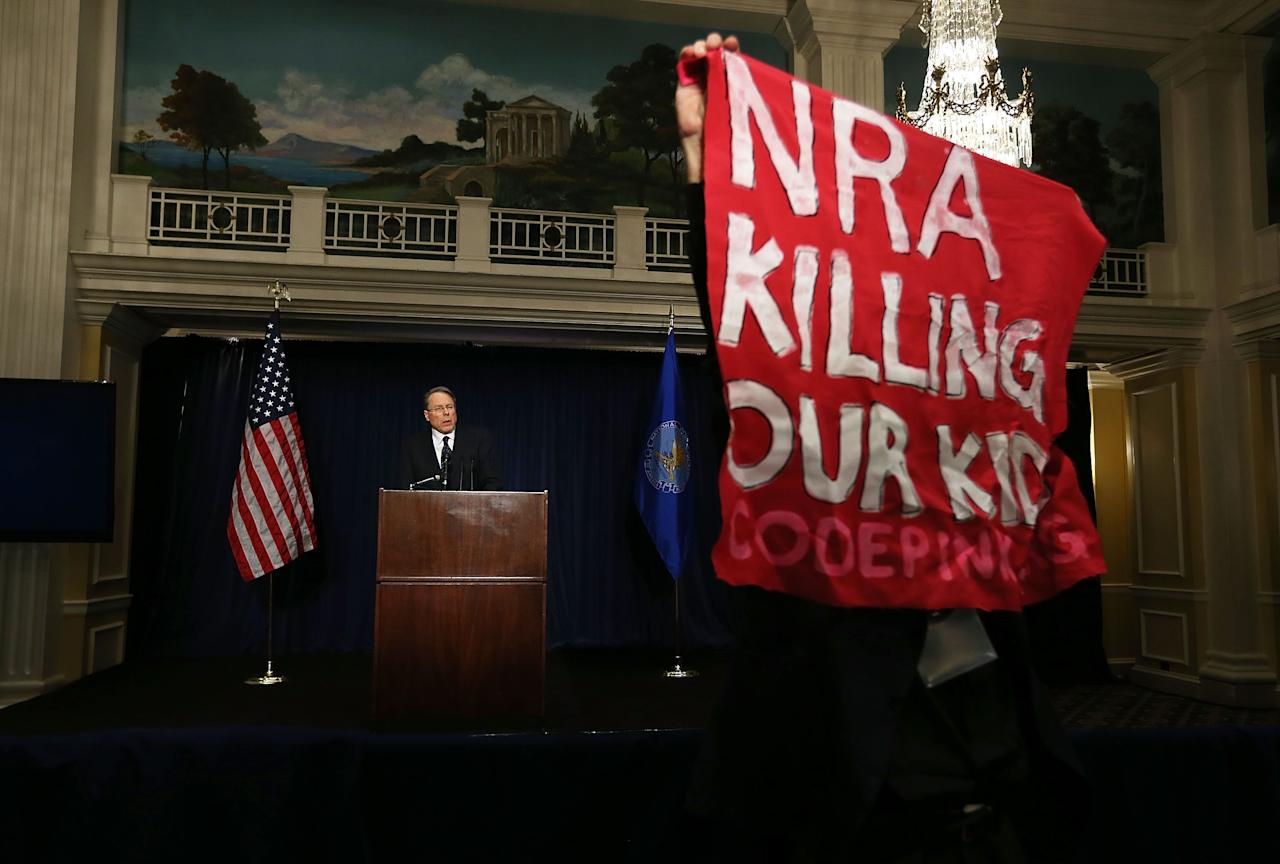 WASHINGTON, DC - DECEMBER 21:  A protester holds up a bannaer as he protests during NRA CEO and Executive Vice President Wayne LaPierre's news conference at the Willard Hotel prior to a news conference the association has scheduled December 21, 2012 in Washington, DC. This is the first public appearance that leaders of the gun rights group have made since a 20-year-old man used a popular assault-style rifle to slaughter 20 school children and six adults at Sandy Hook Elementary School in Newtown, Connecticut, one week ago.  (Photo by Alex Wong/Getty Images)