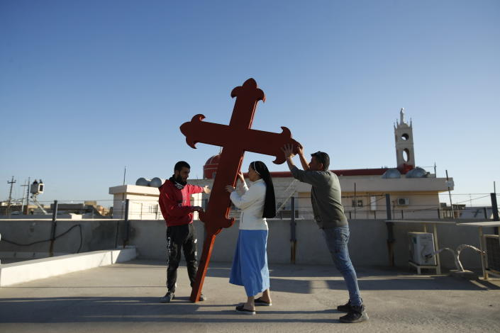 Iraqi Christians place a cross on a church in Qaraqosh, Iraq, Monday, Feb. 22, 2021. Iraq was estimated to have more than 1 million Christians before the 2003 U.S.-led invasion that toppled dictator Saddam Hussein. Now, church officials estimate only few hundred remain within Iraq borders. The rest are scattered across the globe, resettling in far-flung places like Australia, Canada and Sweden as well as neighboring countries. (AP Photo/Hadi Mizban)
