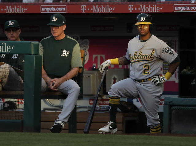 Oakland Athletics' Khris Davis, right, waits for his at-bat, next to manager Bob Melvin during the first inning of the team's baseball game against the Los Angeles Angels on Tuesday, June 4, 2019, in Anaheim, Calif. (AP Photo/Marcio Jose Sanchez)