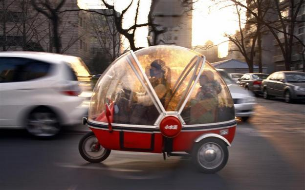A woman and her son sit inside the capsule of an electric tricycle as they drive along a main road in central Beijing March 15, 2012.
