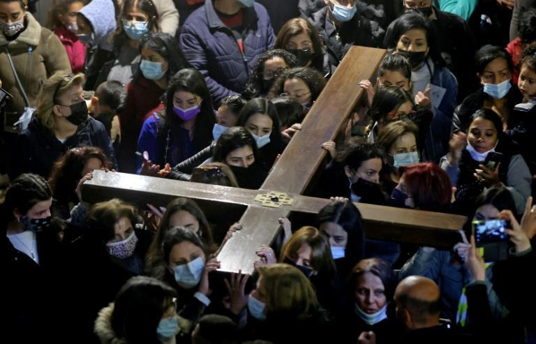 Christian worshippers carrying a wooden cross arrive at the Church of the Holy Sepulchre, during a Good Friday procession along the Via Dolorosa (Way of Suffering) in Jerusalem's Old City