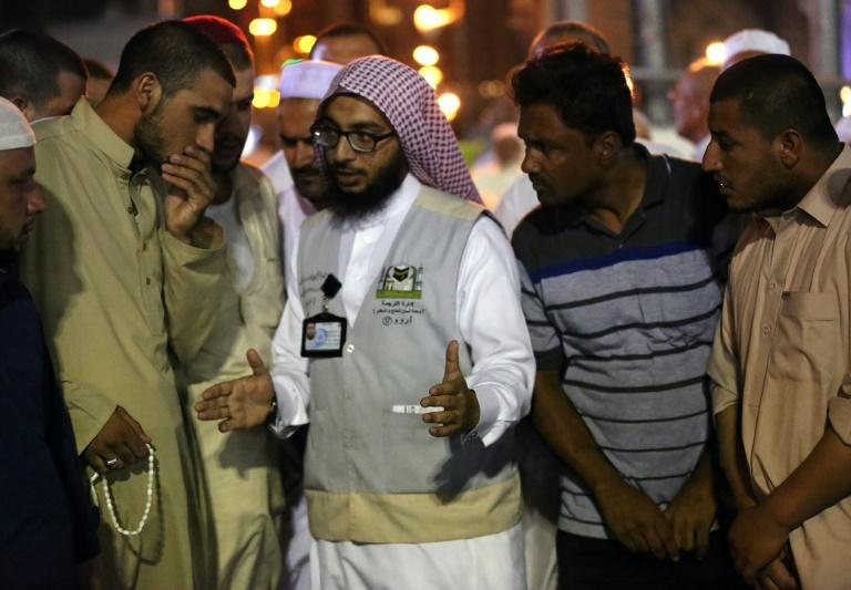 Muslim pilgrims speak to a translator in the Saudi holy city of Mecca on August 17, 2018, ahead of the start of the hajj pilgrimage