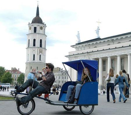 A Lithuanian man drives a city resident in a Velomobile outside the cathedral in Vilnius in this file photo taken August 6, 2004. REUTERS/Liutauras Strimaitis