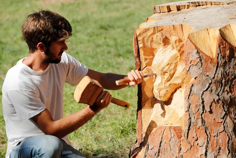 Sculptor Andrea Gandini carves a sculpture of a wolf's face from a dead tree stump in the Villa Pamphili park