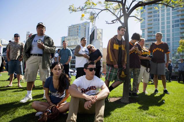Fans look on at a makeshift memorial to former San Diego Padres outfielder Tony Gwynn at Petco Park in San Diego, California June 16, 2014. Gwynn, one of the greatest hitters of his generation, died on Monday at age 54 after a battle with cancer, the National Baseball Hall of Fame and Museum said. REUTERS/Sam Hodgson (UNITED STATES - Tags: SPORT BASEBALL OBITUARY)