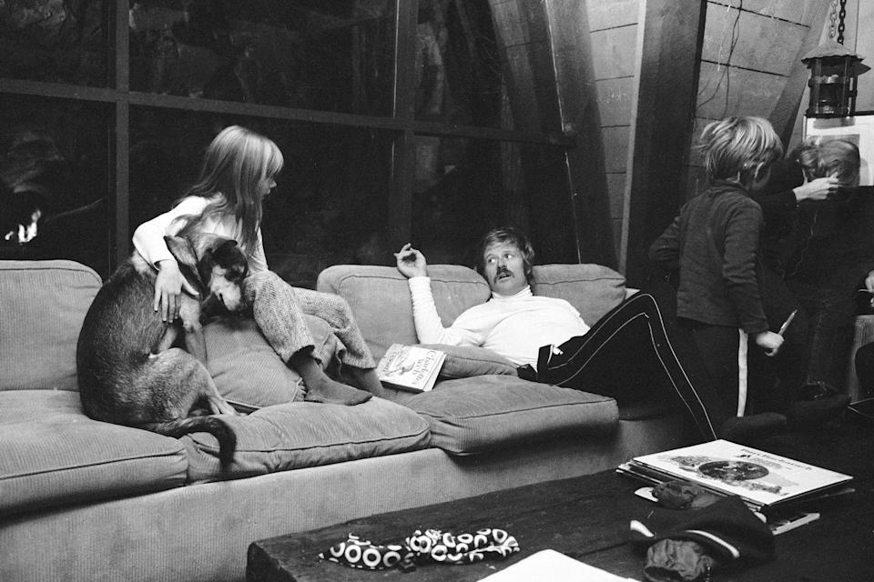 <p>Robert Redford sits on a couch with his daughter Shauna at their Utah home in 1969. His son Jamie and wife Lola Van Wagenen stand to the right. </p>