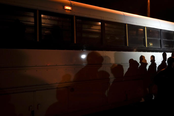 FILE - In this May 11, 2021, file photo shadows of migrants lined up at an intake area are cast along the side of a bus after turning themselves in upon crossing the U.S.-Mexico border in Roma, Texas. President Joe Biden, under political pressure, agreed to admit four times as many refugees this budget year as his predecessor did, but resettlement agencies concede the number actually allowed into the U.S. will be closer to the record-low cap of 15,000 set by former President Donald Trump. (AP Photo/Gregory Bull, File)