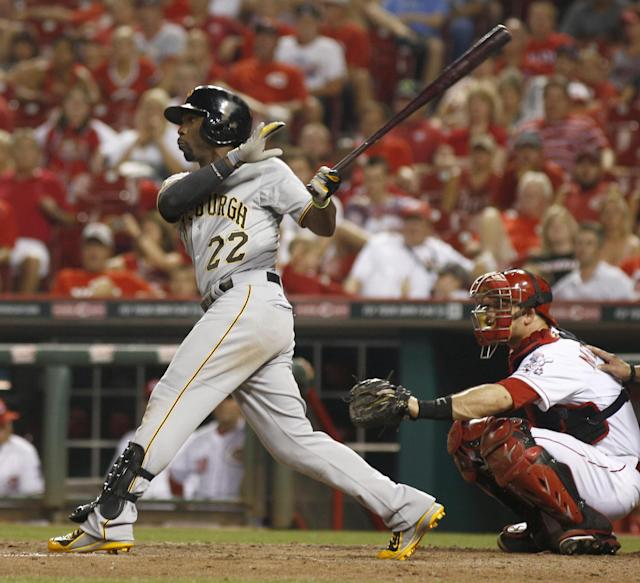 Pittsburgh Pirates' Andrew McCutchen follows through on a solo home run off Cincinnati Reds relief pitcher J.J. Hoover in the 11th inning of a baseball game, Saturday, July 12, 2014, in Cincinnati. Reds catcher Devin Mesoraco is at right. The Pirates won 6-5 in 11 innings. (AP Photo/David Kohl)