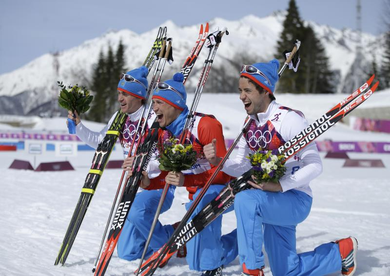 Russia's gold medal winner Alexander Legkov is flanked by Russia's silver medal winner Maxim Vylegzhanin, left and Russia's bronze medal winner Ilia Chernousov during the flower ceremony of the men's 50K cross-country race at the 2014 Winter Olympics, Sunday, Feb. 23, 2014, in Krasnaya Polyana, Russia. (AP Photo/Gregorio Borgia)