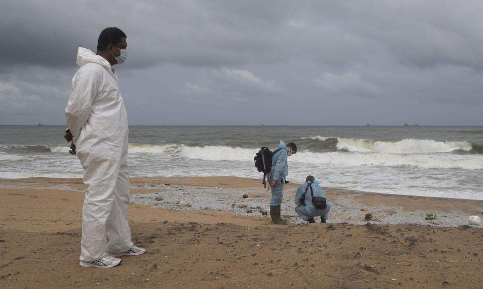 Unidentified foreign investigators inspect debris washed ashore on the beach from the fire-damaged container ship MV X-Press Pearl in Kapungoda, on the out skirts of Colombo, Sri Lanka, Friday, June 4, 2021. Authorities were trying to head off a potential environmental disaster as the Singapore flagged ship that had been carrying chemicals was sinking off of the country's main port. (AP Photo/Eranga Jayawardena)