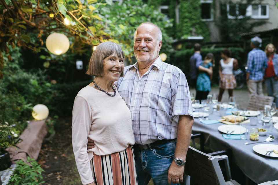A portrait of an elderly couple at a family barbecue smiling.