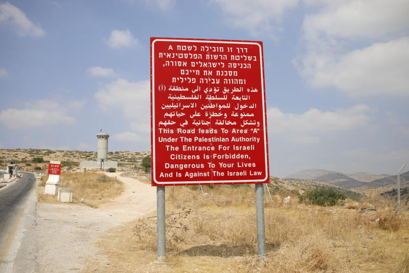 A sign in Hebrew, Arabic and English at an Israeli military roadblock warns against entry to Palestinian-controlled territory, near Bardala in the Israeli-occupied West Bank, Wednesday, Sept. 11, 2019. Israeli Prime Minister Benjamin Netanyahu's election eve vow to annex the Jordan Valley if he is re-elected has sparked an angry Arab rebuke and injected the Palestinians into a campaign that had almost entirely ignored them. (AP Photo/Ariel Schalit)