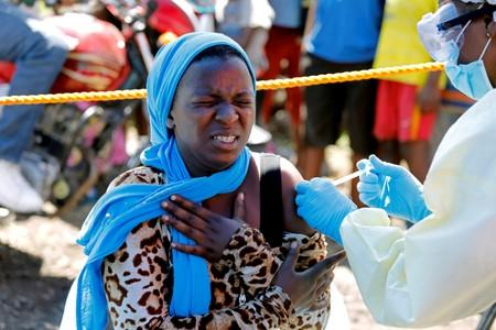 A young woman reacts as a health worker injects her with the Ebola vaccine, in Goma