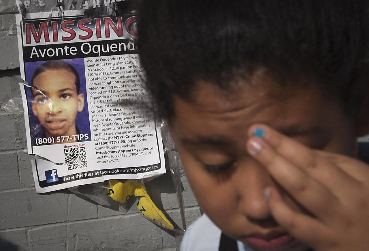 A girl turns around after looking at a missing poster for Avonte Oquendo, a missing 14-year-old autistic boy, on a wall in the Brooklyn borough of New York, October 17, 2013. Oquendo has been missing for 13 days since walking out of his school on October 4, and a $70,000 reward has been offered for his safe return. REUTERS/Carlo Allegri (UNITED STATES - Tags: SOCIETY)
