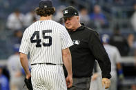 Third base umpire Bill Miller, right, stop inspect New York Yankees starting pitcher Gerrit Cole, left, for foreign substances after the top of the third inning of a baseball game against the Kansas City Royals, Tuesday, June 22, 2021, at Yankee Stadium in New York. (AP Photo/Kathy Willens)