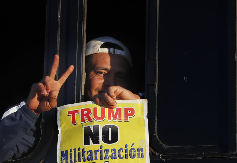 "A migrant traveling with a caravan hoping to reach the U.S. border, holds a sign with a message that reads in Spanish: ""Trump, No to militarization of the border,"" after boarding a bus in La Concha, Mexico, Wednesday, Nov. 14, 2018. Buses and trucks are carrying some migrants into the state of Sinaloa along the Gulf of California and further northward into the border state of Sonora. The bulk of the main caravan appeared to be about 1,100 miles from the border, but was moving hundreds of miles per day. (AP Photo/Marco Ugarte)"
