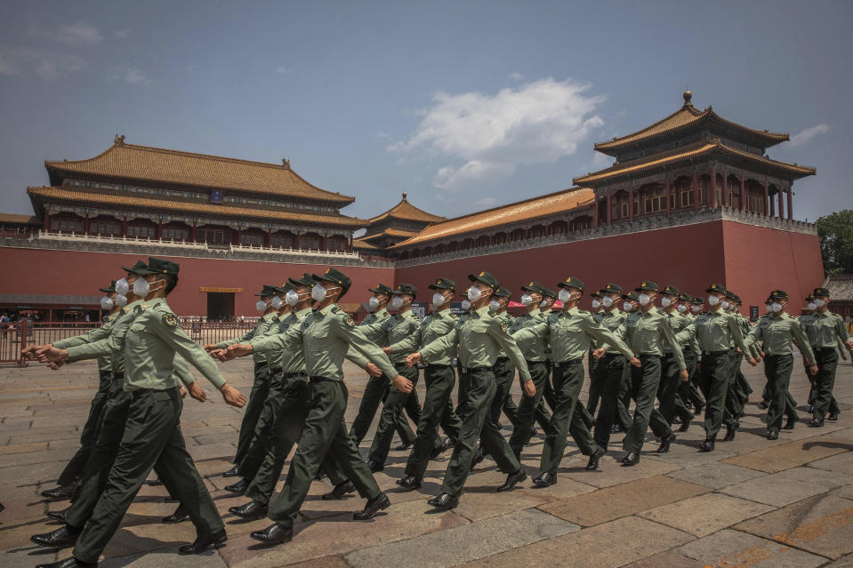 Chinese People's Liberation Army (PLA) soldiers wearing protective face masks march past the entrance to the Forbidden City on the first day of China's National People's Congress (NPC) in Beijing, Friday, May 22, 2020. China held the Chinese People's Political Consultative Conference (CPPCC) on Thursday and the NPC on Friday, after the two major political meetings initially planned to be held in March, 2020 were postponed amid the ongoing new coronavirus  pandemic.  (Roman Pilipey/Pool Photo via AP)