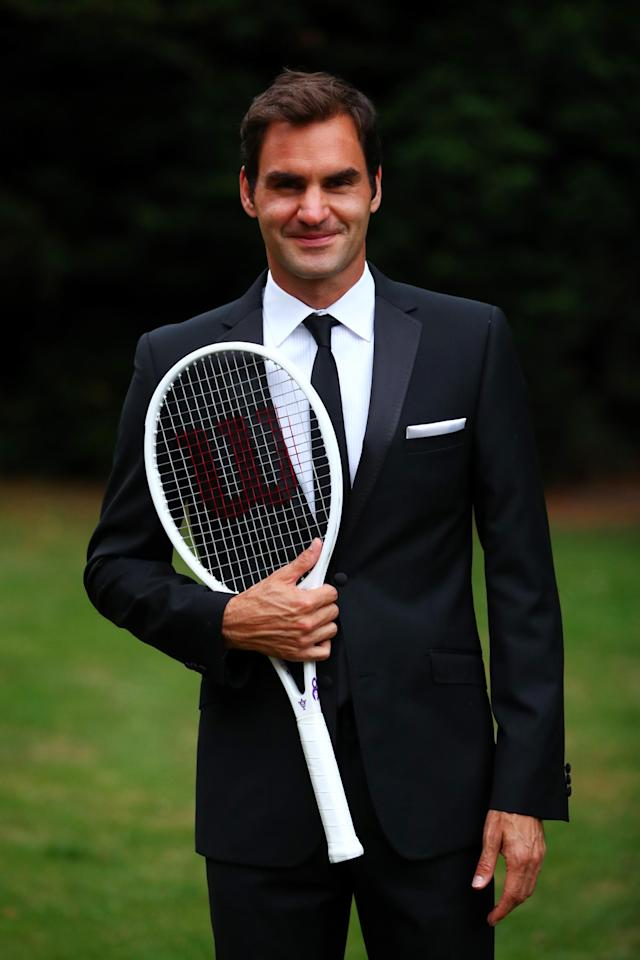 "LONDON, ENGLAND - JULY 16: Roger Federer of Switzerland celebrates his Wimbledon record with an exclusive commemorative ""8"" Wilson tennis racket after his victory against Marin Cilic of Croatia on day thirteen of the Wimbledon Lawn Tennis Championships at the All England Lawn Tennis and Croquet Club on July 16, 2017 in London, England. (Photo by Clive Brunskill/Getty Images for Wilson)"