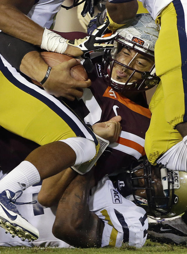 Virginia Tech quarterback Logan Thomas is stopped by the Georgia Tech defense after a short gain in the first half of an NCAA college football game on Thursday, Sept. 26, 2013, in Atlanta. (AP Photo/John Bazemore)