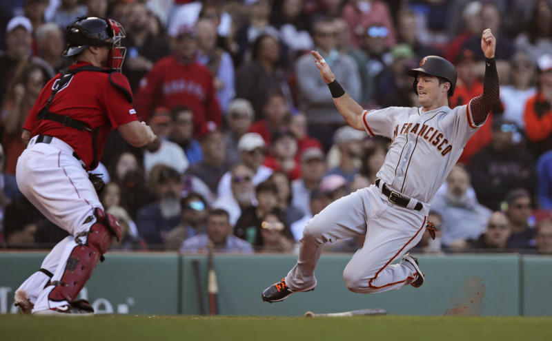San Francisco Giants' Mike Yastrzemski, right, beats the throw and tag by Boston Red Sox catcher Christian Vazquez to score on a double by Kevin Pillar during the eighth inning of a baseball game at Fenway Park in Boston, Thursday, Sept. 19, 2019. (AP Photo/Charles Krupa)