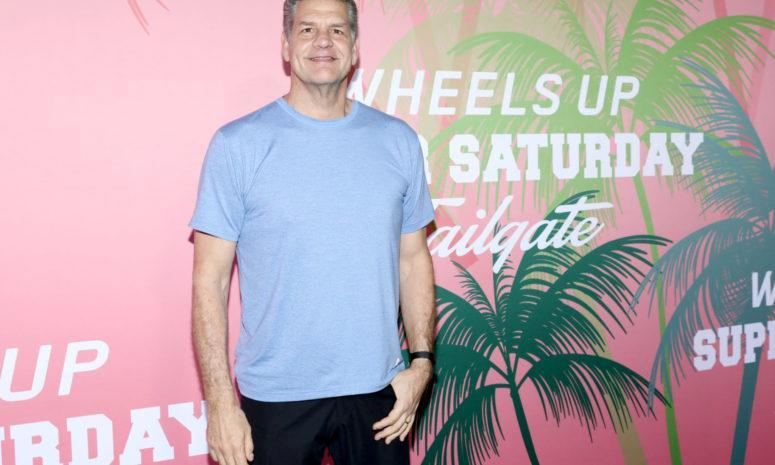 Mike Golic stands in front of a billboard.