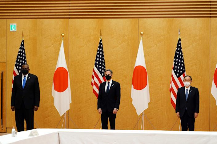 """Japan's Prime Minister Yoshihide Suga (R) poses with U.S. Secretary of State Antony Blinken (C) and U.S. Defense Secretary Lloyd Austin (L) during a courtesy call at the prime minister's official residence in Tokyo on March 16, 2021.<span class=""""copyright"""">Eugene Hoshiko—POOL/AFP/Getty Images</span>"""