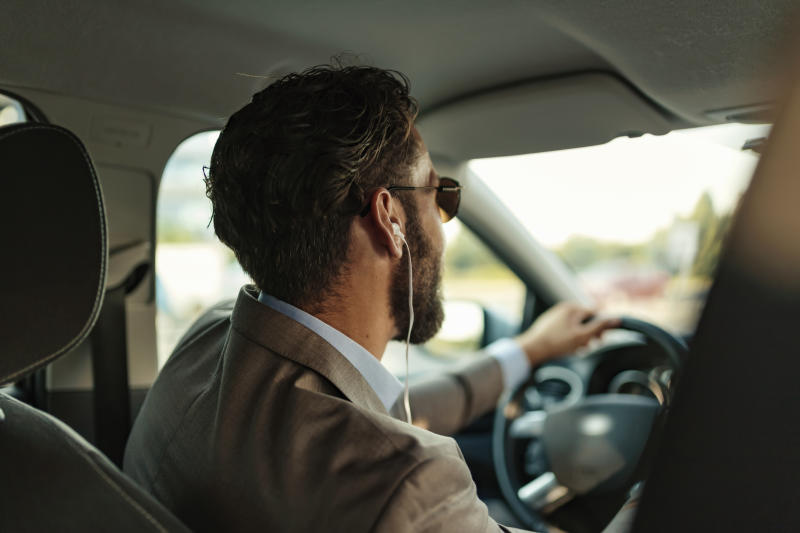 A handsome businessman in a full suit wearing headphones while driving his car.