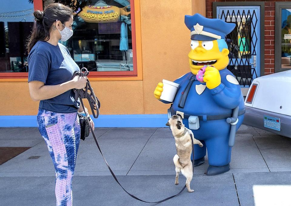 """A person with a dog on a leash. The dog looks at a """"Simpsons"""" character statue."""