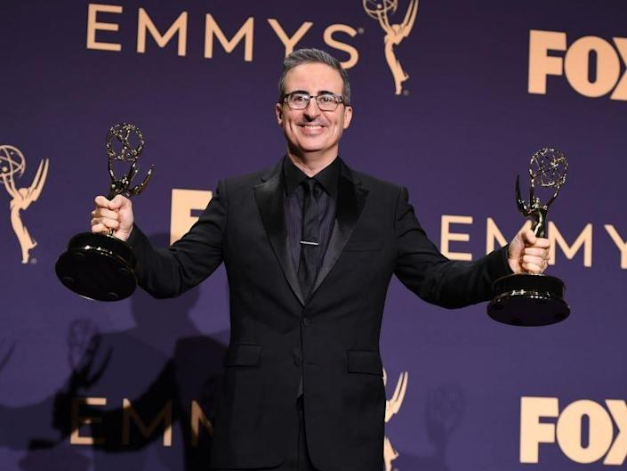 John Oliver holds Emmy awards in each hand at the 2019 Emmys.