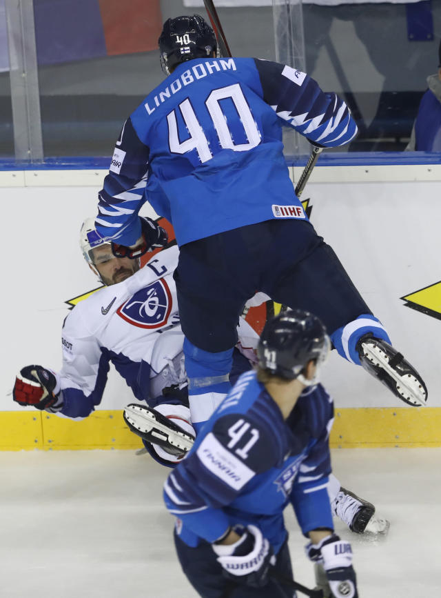 Finland's Joel Kiviranta, down, looks back as Finland's Petteri Lindbohm, right, checks Damien Fleury of France, left, during the Ice Hockey World Championships group A match between France and Finland at the Steel Arena in Kosice, Slovakia, Sunday, May 19, 2019. (AP Photo/Petr David Josek)