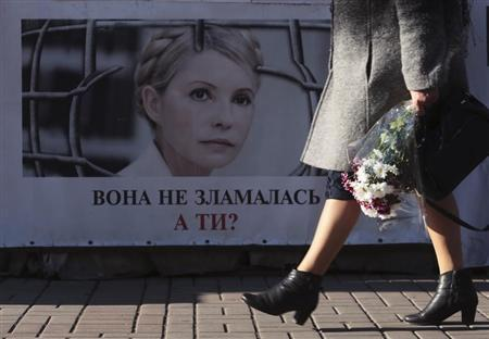 A woman walks past a portrait of jailed former Ukrainian PM and opposition leader Tymoshenko at a protest tent camp set up by her supporters in central Kiev