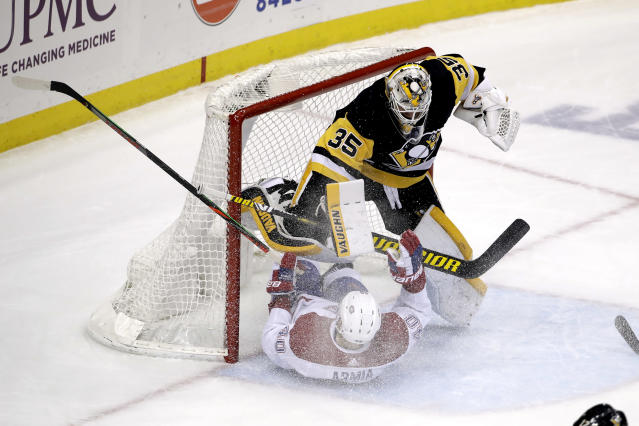 Montreal Canadiens' Joel Armia (40) collides with Pittsburgh Penguins goaltender Tristan Jarry (35) during the first period of an NHL hockey game in Pittsburgh, Friday, Feb. 14, 2020. (AP Photo/Gene J. Puskar)